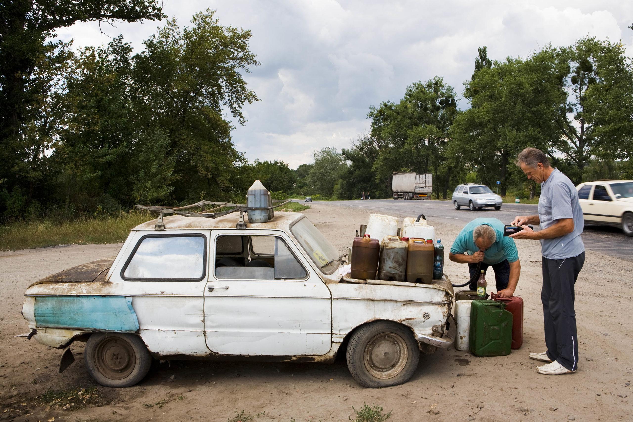Zaporozhets. Leonti Michailovitsj sells stolen diesel from his car. Karatsjivka, Ukraine, 2008