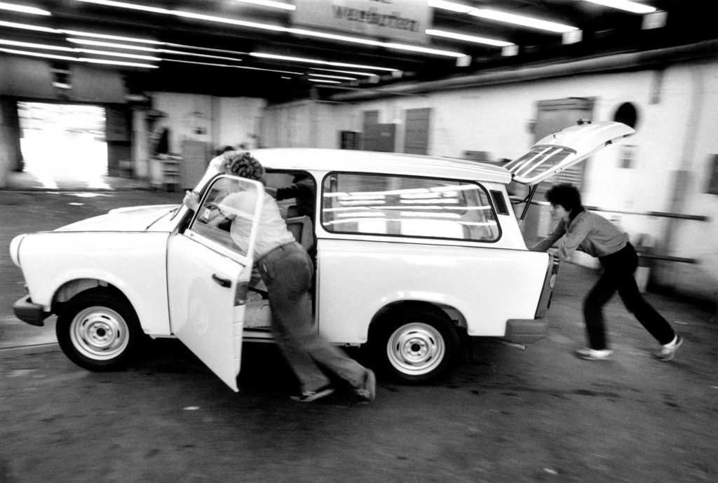 Workers push a complete Trabant out of final assembly, 1991